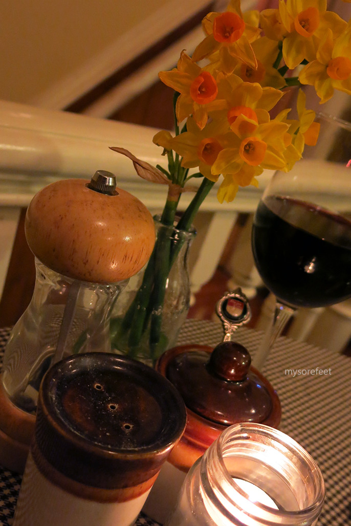 Simple table setting of salt, sugar, pepper, a candle and a small bunch of flowers. The red wine belongs to The Snowman.